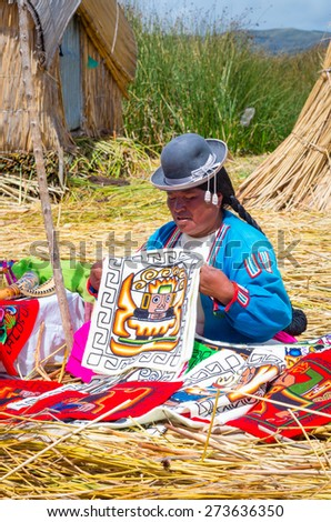 TITICACA, PERU, MARCH 19, 2015: Local women in traditional attire work sell handicrafts to tourists at Uros islands on Titicaca lake in Peru. - stock photo