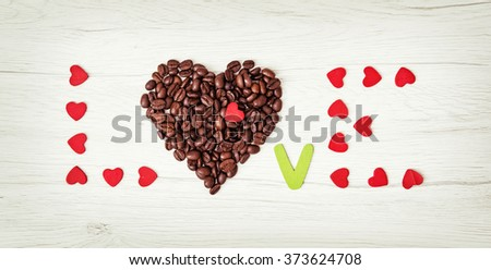 Title LOVE of coffee beans and many little red hearts on the wooden background. Valentine's Day. Symbol of love. - stock photo