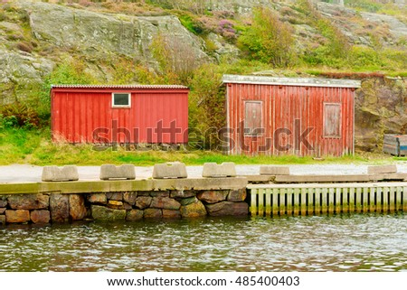 Tjorn, Sweden - September 9, 2016: Environmental documentary of two weathered seaside sheds in harbor area.
