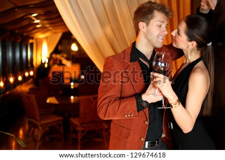 to a good girl flirting young man with a glass of wine - stock photo