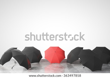 To be unique concept with many black umbrellas and one red on concrete floor - stock photo