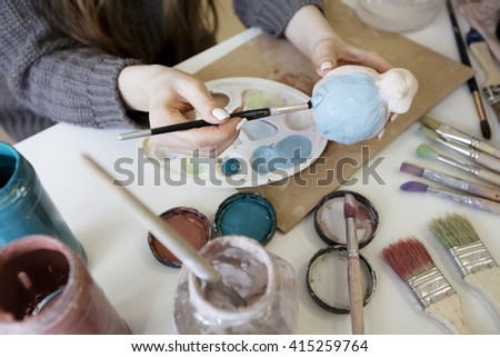 to decorate a toy from clay. Female hands with the brush and the clay. - stock photo