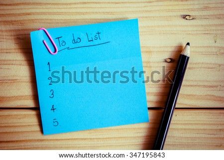 To do list on colorful sticky note on wooden background