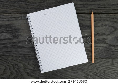 to do list phrase in notepad with chequered pages on gray wood table and pencil, top view - stock photo
