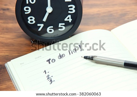 To do list  with a pen amd alarm clock on wood background