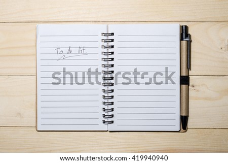 To do list  with a pen on wood background