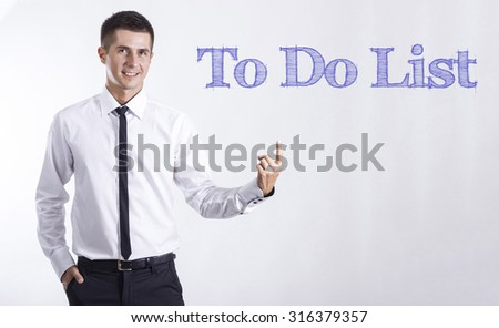 To Do List - Young smiling businessman pointing on text