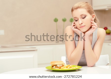 To eat or not to eat. Confused young lady watching at the plate with fast-food lunch wants to eat it - stock photo