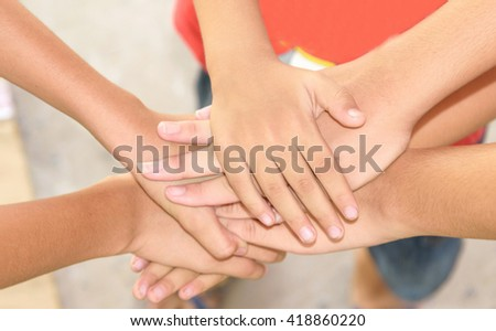 To join hands to show unity and team spirit. - stock photo