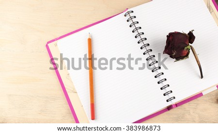 To keep a diary. Romantic memories. The opened diary on a spring, simple pencil and faded red roses on wooden background