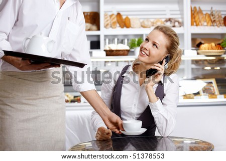 To the girl speaking on the phone bring a coffee cup - stock photo