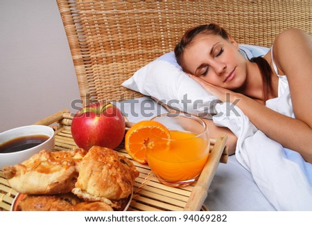 To the sleeping woman have brought a breakfast in bed - stock photo
