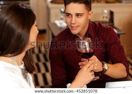 To us! Cropped closeup of a gorgeous young couple cheering with their wine glasses on a date at the restaurant - stock photo