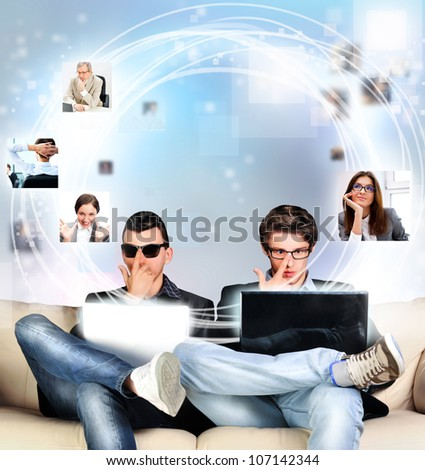 To young men sitting at home on couch and using their laptops to work with internet and social media. They are looking for new friends and communicating old ones - stock photo