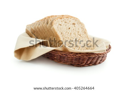 Toast bread in a basket. Wholemeal toast bread slices placed on a cotton cloth napkin in a wicker basket close up isolated on white background. - stock photo