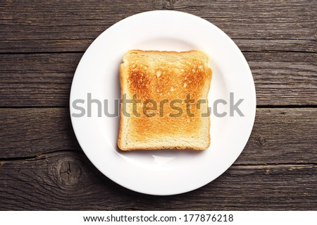 Toast bread in a white plate on vintage wooden background. Top view - stock photo