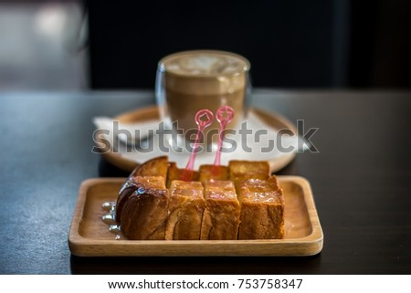 Toast bread with butter and sweetened condensed milk on Wood Tray. have Latte is blackground.