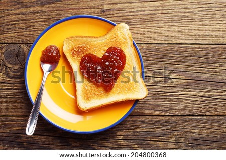 Toast bread with jam in shape of hearts on vintage wooden table. Top view - stock photo