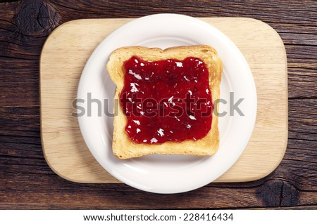 Toast bread with raspberry jam in white plate on cutting board. Top view - stock photo