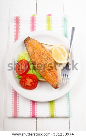 toast bread with smoked mackerel, tomato, salad and lemon on a plate - stock photo