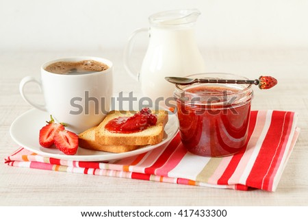 Toast bread with strawberry jam, coffee and glass of milk on wooden table
