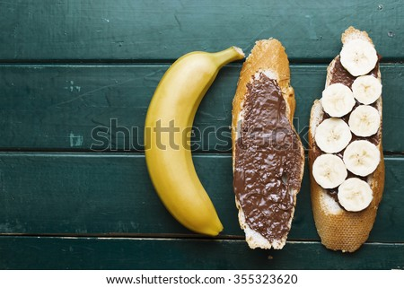toast, chocolate spread with bread and banana slices, whole yellow banana on bright wooden table. healthy food breakfast, tasty concept. selective focus, toned image - stock photo