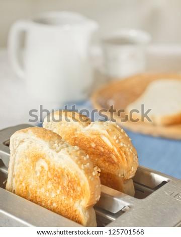 Toast in toaster in simple breakfast setting - stock photo
