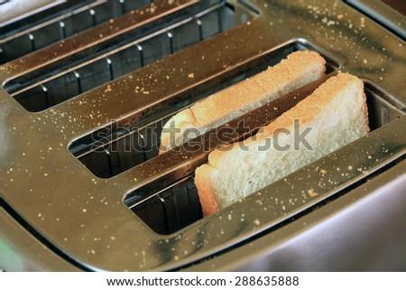 Toast in Toaster in Simple Breakfast Setting. - stock photo