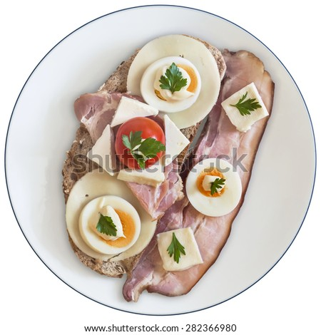 Toast Sandwich in white porcelain plate, with Pork Bacon Rasher, Ham, Edam and White cow cheese, hard boiled Egg slices, Cherry Tomato, Mayonnaise and Parsley leaves, isolated on White Background. - stock photo