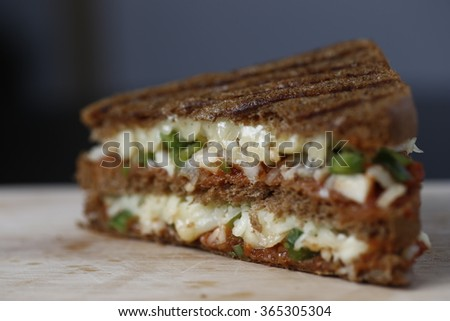 toast sandwich is made by putting a thin slice of toast between two slices of bread with a layer of butter adding salt and pepper. This quick and tasty ham and cheese toasted sandwich packs nutrition - stock photo