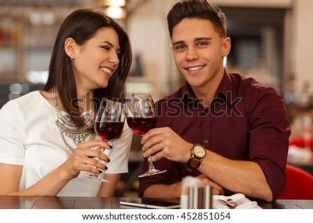 Toast to love. Handsome young man smiling to the camera while toasting wine glasses with his gorgeous happily laughing girlfriend on a date at a fancy restaurant - stock photo