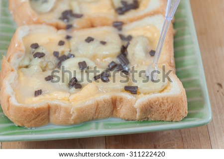 Toast topped with banana ,Sweetened condensed milk, chocolate and sugar on the wooden.Selective focus. Very shallow Depth of Field, for soft background.