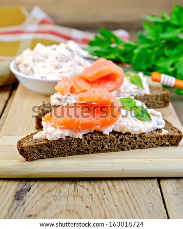 Toast two slices of rye bread with cream, basil and salmon, knife, napkin, parsley on a wooden boards background - stock photo