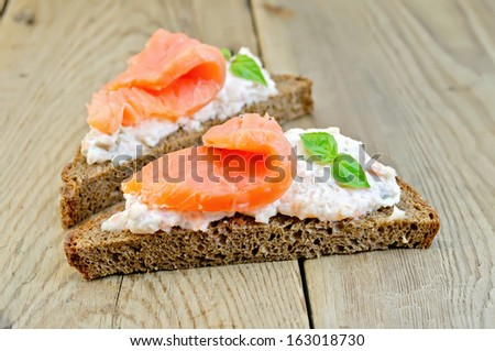 Toast two slices of rye bread with cream, basil and salmon on the background of wooden boards - stock photo