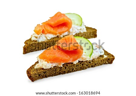 Toast two slices of rye bread with cream, salmon and cucumber isolated on white background - stock photo