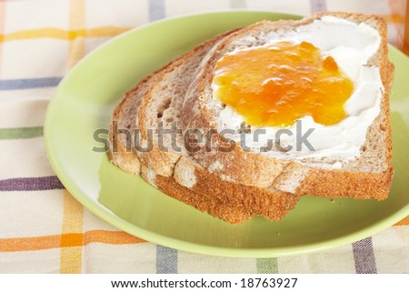 Toast with butter and peach jam in the green plate with soft shadow on square mat background. Shallow depth of field