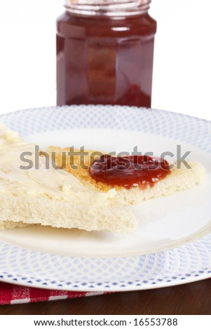 Toast with butter and strawberry jam glass jar in the white plate with soft shadow on square mat background. Shallow depth of field