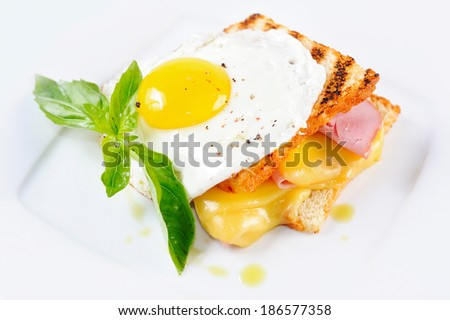 toast with cheese and meat on top of scrambled eggs with herbs - stock photo