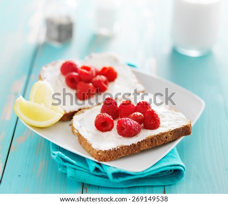 toast with cream cheese and fresh raspberries - stock photo