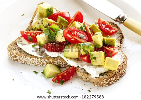 Toast with cream cheese, avocado and cherry tomatoes - stock photo