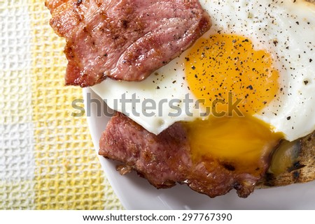 Toast with fried eggs and bacon on a white plate - stock photo