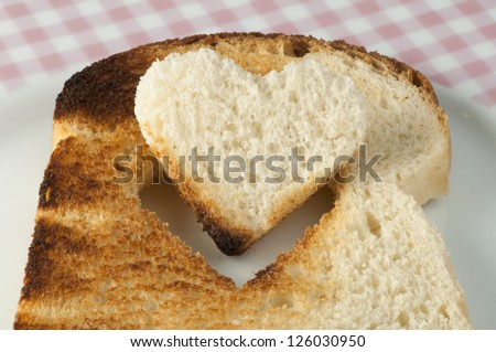 Toast with heart-shaped set in white plate - stock photo