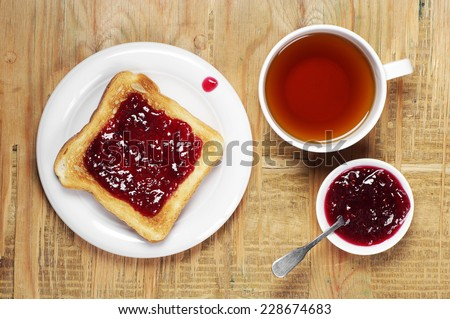 Toast with jam and cup of tea on old wooden table. Top view