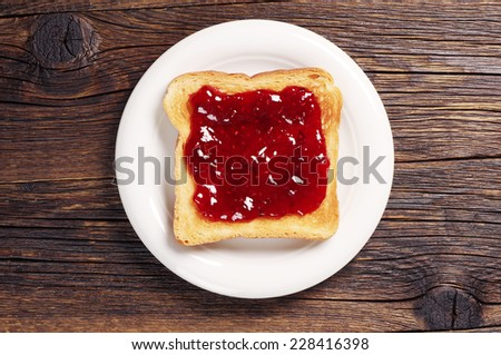Toast with jam in white plate on dark wooden table. Top view - stock photo
