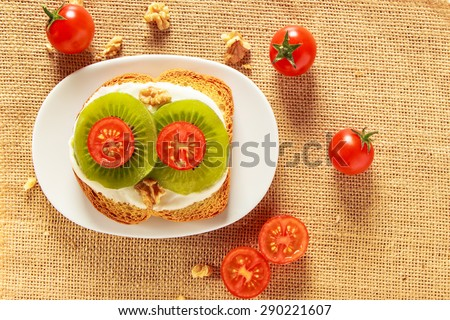 Toast with kiwi, cheese and cherry tomato  on a piece of sackcloth with walnuts and cherry tomatoes around. View from above