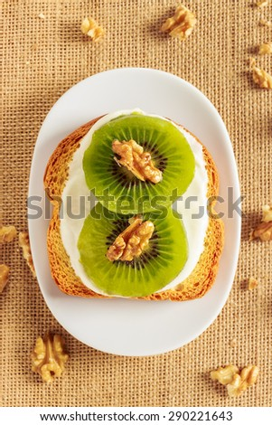 Toast with kiwi, cheese and walnuts on a piece of sackcloth with walnuts around. View from above