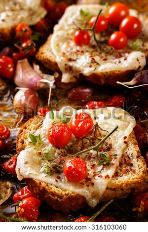 Toast with melted cheese, cherry tomatoes and aromatic herbs - stock photo