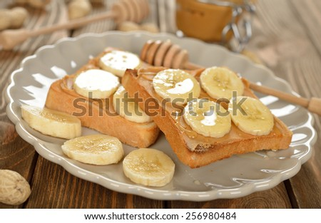 Toast with peanut butter and banana on a brown table - stock photo