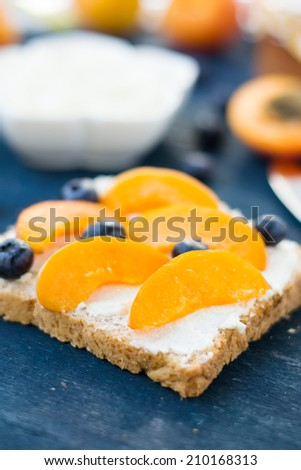 Toast with ricotta cheese and apricots on a wooden table