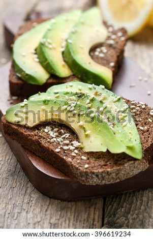toast with slices of avocado and spices, sesame seeds on a wooden background - stock photo